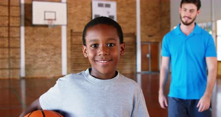 basketbal : Slow motion van sportleraar stond met zijn leerling in basketbal op school gym 4k