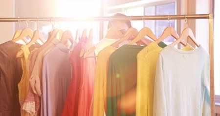munkaruha : Fashion designer looking at clothes rail in her store 4k Stock mozgókép