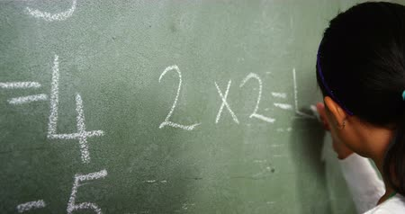 çözme : Portrait of schoolgirl doing mathematics on chalkboard in classroom at school 4k