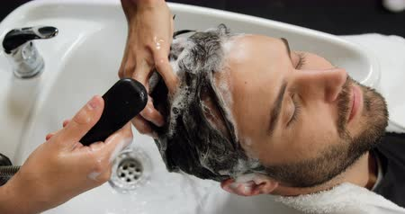 şampuan : Man getting his hair wash at a salon 4k Stok Video
