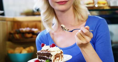 desszertek : Beautiful woman eating sweet dessert in cafeteria 4k