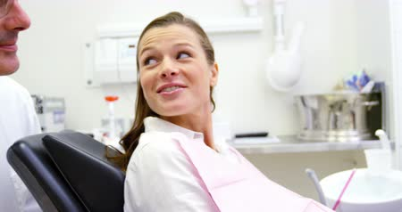 назначение : Smiling dentist talking to female patient in dental clinic 4k