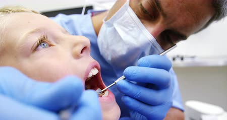 dentysta : Dentist examining a young patient with tools in dental clinic 4k