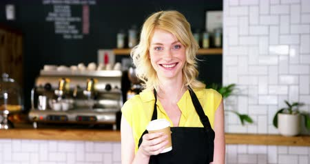 garçonete : Portrait of waitress holding disposable coffee cup in cafeteria 4k