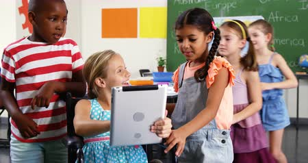 ler : Smiling schoolkids using digital tablet in classroom at school 4k