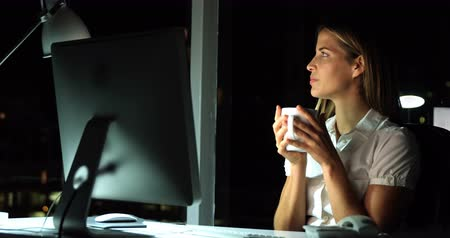 komputer stacjonarny : Businesswoman having coffee while working over computer in office 4k