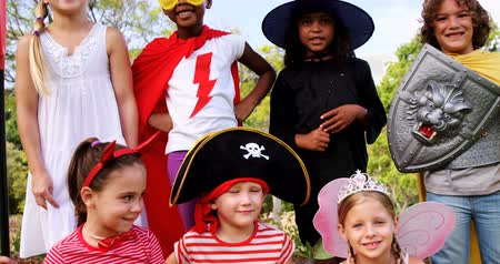 kostüm : Portrait of group of kids in various costumes in the park 4k