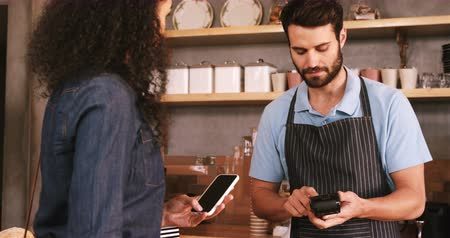 counter : Woman paying bill through smartphone using NFC technology in cafe 4k