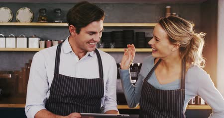 restoran : Smiling waiter and waitress using digital tablet while talking to each other in the cafe 4k