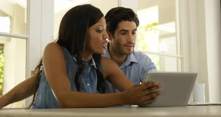 looking : Couple interacting with each other while using digital tablet at home 4k