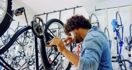 szerelő : Smiling mechanic repairing bicycle in workshop 4k