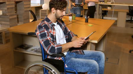 инвалидность : Male business executive sitting on wheelchair and using digital tablet in office 4k Стоковые видеозаписи