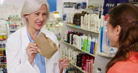 фармацевт : Pharmacist packing medicine in paper bag for customer in pharmacy