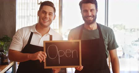 текст : Portrait of smiling waiters showing slate with open sign in café 4k