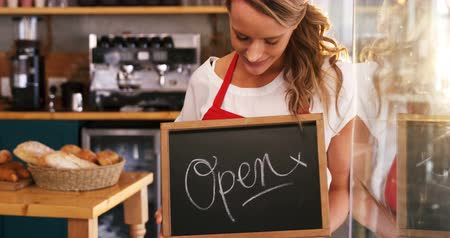 garçonete : Smiling waitress holding a open sign board in cafe 4k