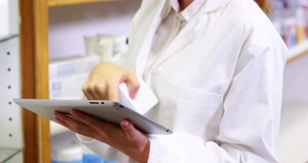 dispensary : Pharmacist using digital tablet while checking medicine in pharmacy