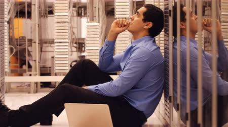 technikus : Stressed technician sitting in hallway of server room 4k