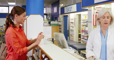gyógyszertár : Pharmacist assisting the bottle of drug to customer in pharmacy