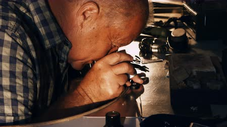 appraising : Close-up of goldsmith?examining diamond through loupe in workshop 4k