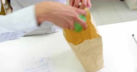 dispensary : Pharmacists packing medicine in paper bag at pharmacy Stock Footage