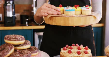 holding : Mid-section of waitress holding cup cake on tray in café 4k Stock Footage