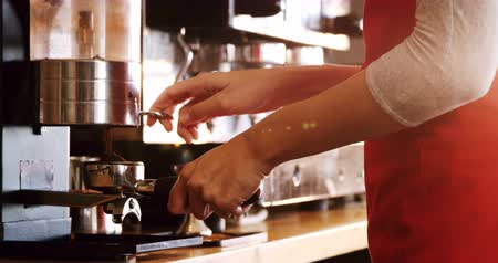 portafilter : Mid section of waiter holding portafilter filled with ground coffee in café 4k Stock Footage