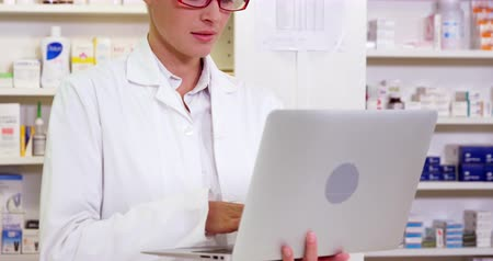 dispensary : Pharmacist standing at counter and using laptop in pharmacy Stock Footage