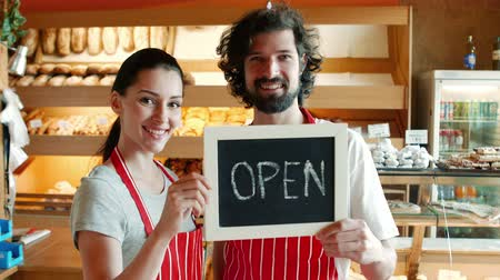 bakery : Portrait of bakers holding open signboard in the bakery shop 4k Stock Footage