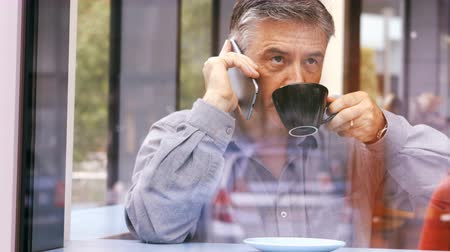 cellphone : Businessman talking on mobile phone while having cup of coffee in office cafeteria 4k