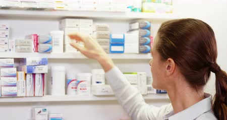 фармацевт : Pharmacist checking medicine in shelf at pharmacy