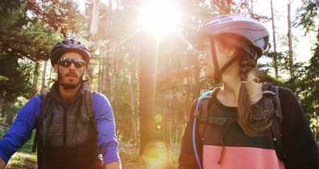 tonları : Mountain biking couple pointing at nature in the forest 4k