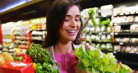 grocery : Happy woman holding grocery bag in grocery section of supermarket
