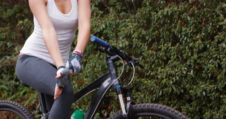 cyclists : Female cyclist wearing sports gloves in forest
