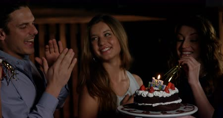 doğum günü : Slow motion of smiling friends blowing candle while celebrating birthday in bar 4k Stok Video