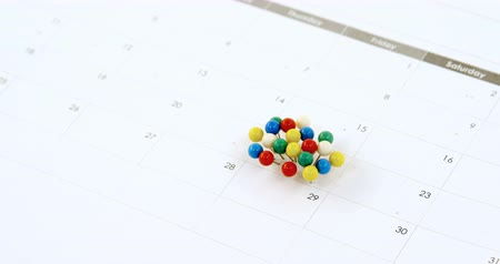 rajzszeg : Close-up of multicolored push pin marked on calendar 4k Stock mozgókép