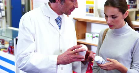 dispensary : Pharmacist assisting the bottle of drug to customer in pharmacy 4k