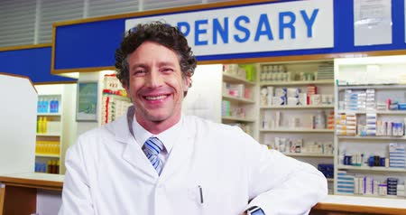 dispensary : Portrait of happy pharmacist standing at counter in pharmacy 4k Stock Footage