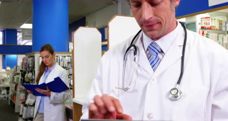 dispensary : Pharmacist using digital tablet while colleague standing background in pharmacy 4k