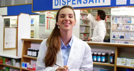 dispensary : Portrait of pharmacist writing on notepad in pharmacy 4k