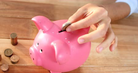 colocando : Close-up of woman putting coin in piggy bank 4k