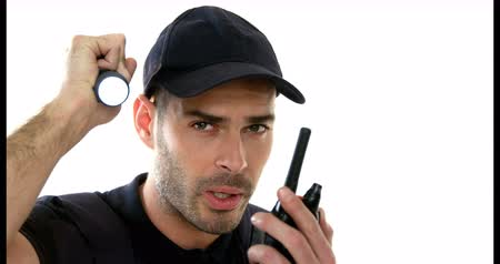 bulletproof : Security guard holding torch while talking on walkie talkie on white background 4k
