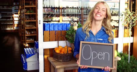proprietário : Portrait of smiling owner holding open signboard in supermarket 4k
