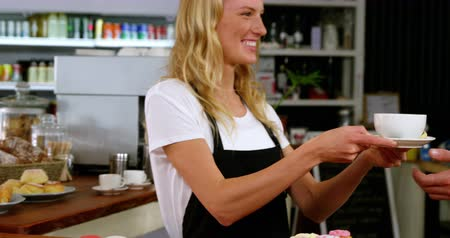 porce : Smiling waitress serving cup of coffee to customer in café 4k
