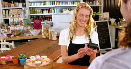 counter : Customer making payment through payment terminal machine at counter in café 4k Stock Footage