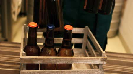 craft beer : Mid-section of brewer putting beer bottle in beer crate at brewery Stock Footage