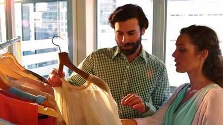 roupas : Couple selecting a dress while shopping for clothes in a clothing store Stock Footage