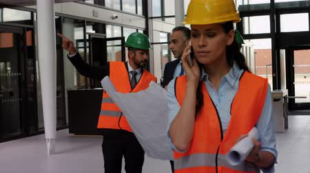 planos : Female architect talking on mobile phone in office while colleagues discussing over blueprints 4k Stock Footage