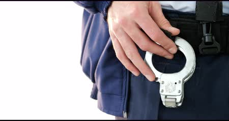 kajdanki : Mid section of security guard holding handcuffs on white background 4k Wideo
