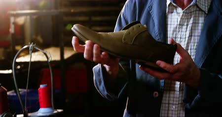 warsztat : Shoemaker examining a shoe in workshop 4k