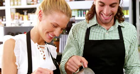 garçonete : Smiling waiter and waitress making cup of coffee at counter